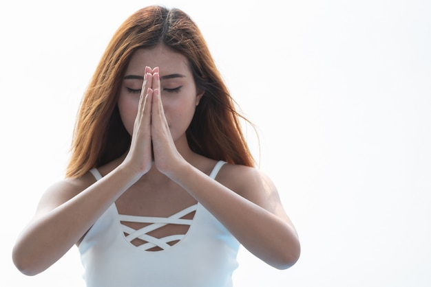 Joga kobieta medytuje z trzymać ręki wpólnie na białym tle. Premium Zdjęcia