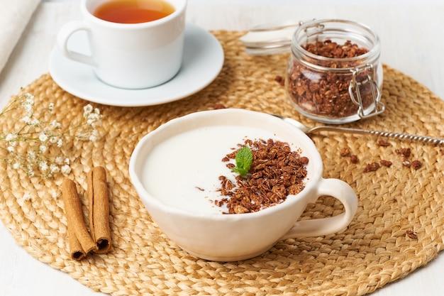 Jogurt Z Czekoladową Granolą W Filiżance, śniadanie Z Herbatą Na Beżu Premium Zdjęcia