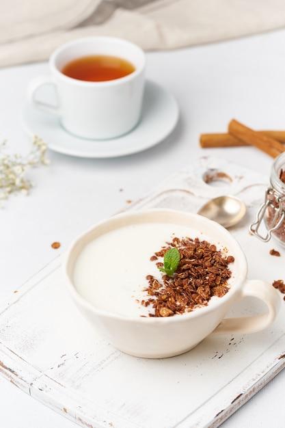 Jogurt Z Czekoladowym Granola W Filiżance, śniadanie Z Herbatą Na Białym Drewnianym Tle, Pionowo. Premium Zdjęcia