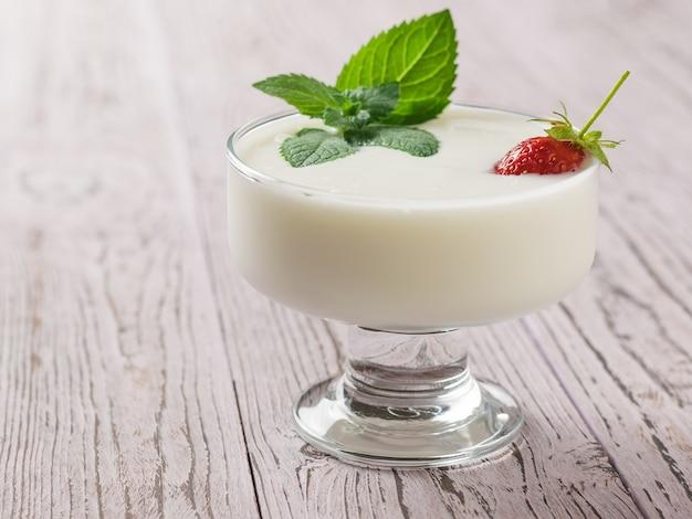 Jogurt Z Truskawkami I Miętą Na Drewnianym Stole Premium Zdjęcia