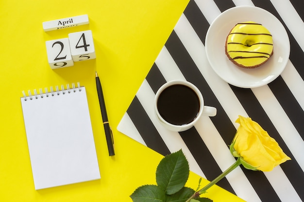 Kalendarz 24 kwietnia. filiżanka kawy, pączek i róża, notatnik do tekstu. koncepcja stylowe miejsce pracy Premium Zdjęcia