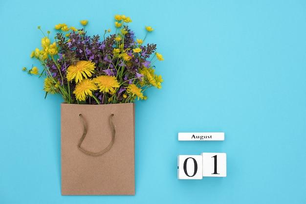 Kalendarz kostki 1 sierpnia i kolorowe kwiaty rustykalne w pakiecie rzemiosła na niebieskim tle Premium Zdjęcia
