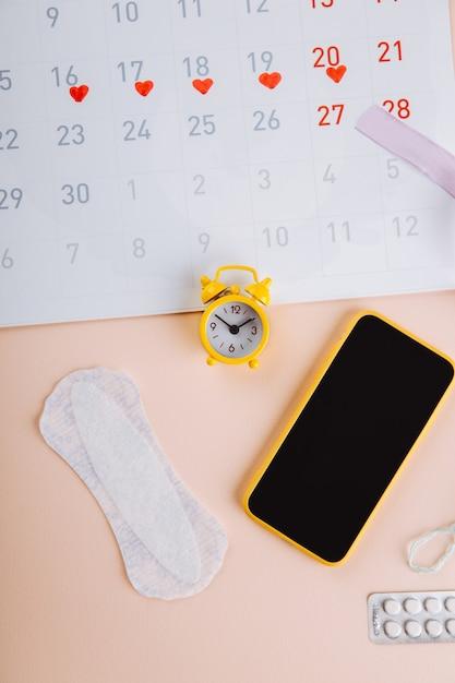 Kalendarz Miesiączkowy I Smartfon Z Podpaską I żółtym Budzikiem Na Różowym Tle. Krytyczne Dni Kobiety, Ochrona Higieny Kobiety. Premium Zdjęcia
