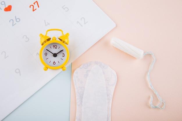 Kalendarz Miesiączkowy Z Podpaskami, Budzikiem I Bawełnianym Tamponem. Koncepcja Okresu Menstruacji. Lek Przeciwbólowy Na Bóle Menstruacyjne. Premium Zdjęcia