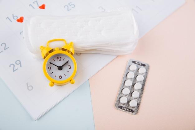 Kalendarz Miesiączkowy Z Podpaskami, Budzikiem I Tabletkami Antykoncepcyjnymi. Koncepcja Okresu Menstruacji. Lek Przeciwbólowy Na Bóle Menstruacyjne. Premium Zdjęcia