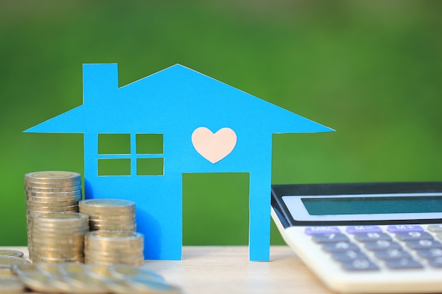 Kalkulator hipoteczny, model niebieski dom i stos monet pieniędzy Premium Zdjęcia