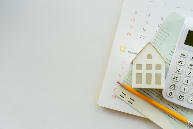Kalkulator, Model Domu, żółty Ołówek, Książka Bankowa I Kalendarz Na Białym Tle Do Kredytu Mieszkaniowego Premium Zdjęcia