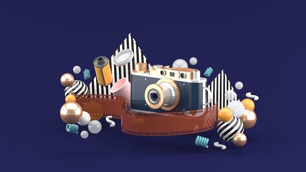 Kamera Filmowa Otoczona Filmem I Kolorowymi Kulkami Na Fioletowej Przestrzeni Premium Zdjęcia