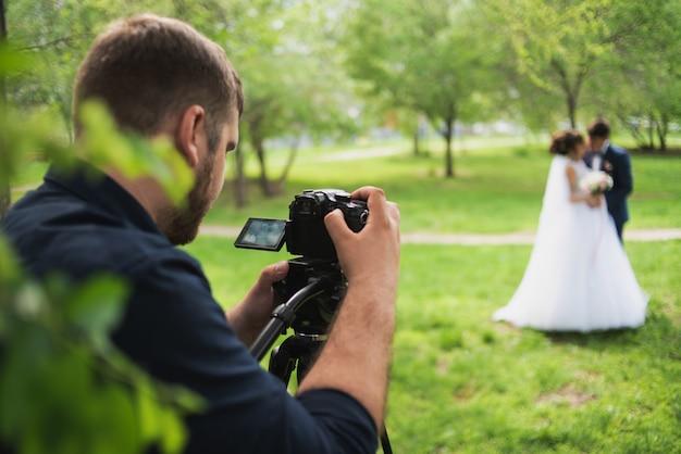 Kamerzysta Filmuje Latem Małżeństwa W Ogrodzie. Premium Zdjęcia