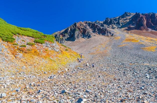 Kamienne zbocze wulkanu z pieszymi turystami. Premium Zdjęcia
