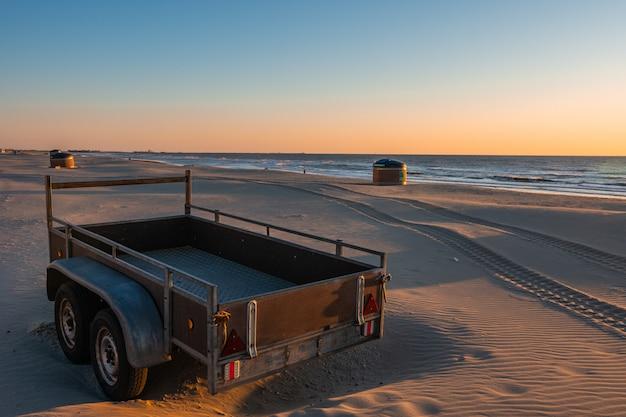 Kamper Lub Przyczepa Na Piaszczystej Plaży W Pięknym Zachodzie Słońca Z Spokojnym Morzem W Premium Zdjęcia