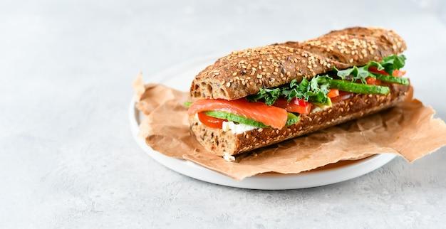 Kanapka z awokado, łososiem, twarogiem, pomidorami i liśćmi sałaty Premium Zdjęcia