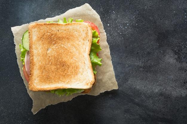 Kanapka z boczkiem, pomidorem, cebulą, sałatką na czarno Premium Zdjęcia