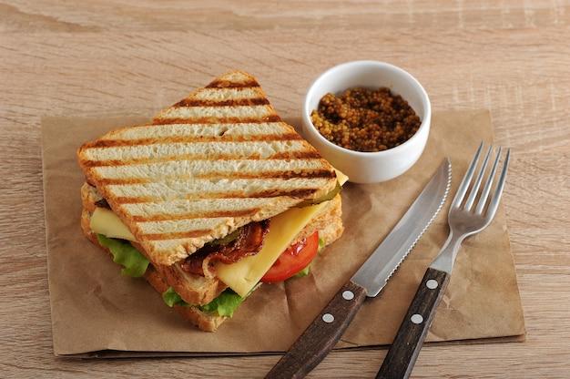 Kanapka z boczkiem, serem, pomidorem i musztardą dijon Premium Zdjęcia