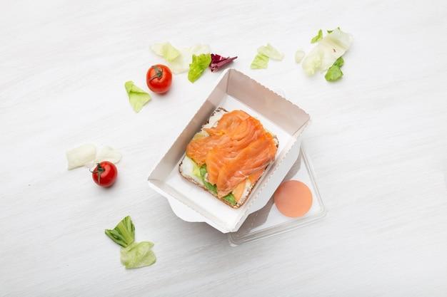 Kanapka Z Widokiem Z Góry Z Miękkim Serem I Czerwoną Rybą Leży W Pudełku Na Lunch Obok Warzyw I Pomidorów Na Białym Stole. Pojęcie Zdrowej Przekąski. Premium Zdjęcia