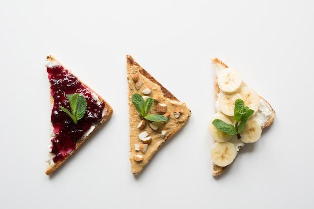 Kanapki na zdrowe i bezcukrowe śniadanie dla dzieci, pasta orzechowa, banany, konfitura jagodowa. Premium Zdjęcia