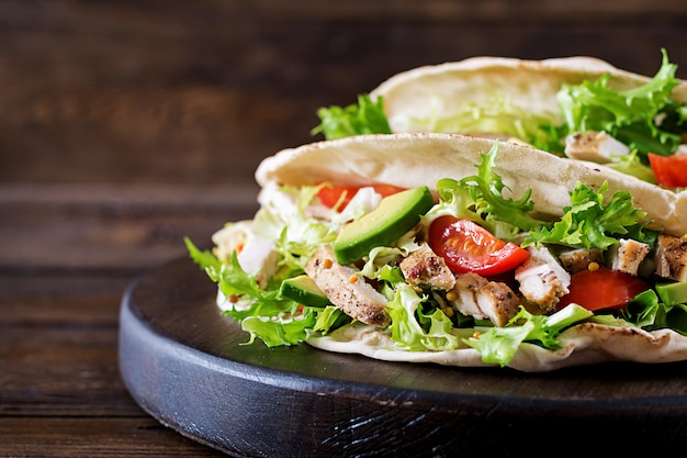 Kanapki Z Chleba Pita Z Grillowanym Mięsem Z Kurczaka, Awokado, Pomidorem, Ogórkiem I Sałatą Podawane Na Drewnianym Stole Darmowe Zdjęcia