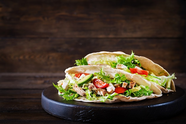 Kanapki Z Chlebem Pita Z Grillowanym Mięsem Z Kurczaka, Awokado, Pomidorem, Ogórkiem I Sałatą Podawane Na Drewniane Tła. Premium Zdjęcia