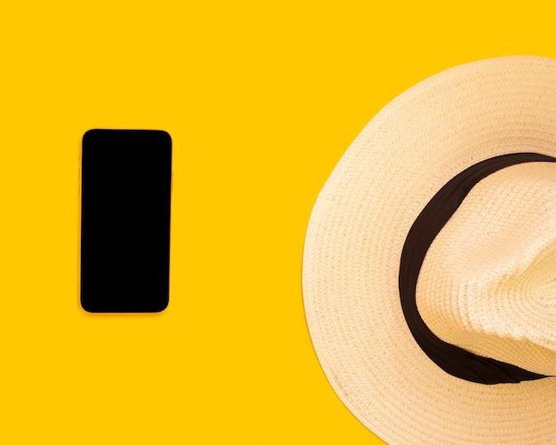 Kapelusz, Smartphone, żółte Tło, Pojęcie Podróży Premium Zdjęcia