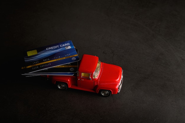 Karta kredytowa w czerwonym modelu pickupa na czarnej podłodze Darmowe Zdjęcia