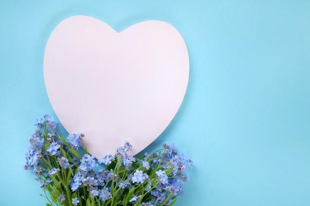 Karta kwiatowa niezapominajka kwiaty i różowe serce puste w pastelowym niebieskim Premium Zdjęcia