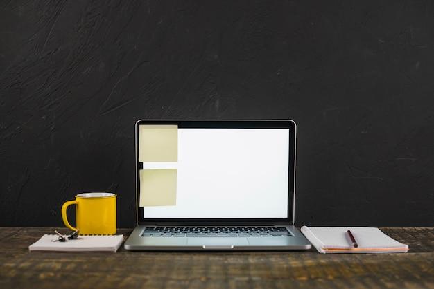 Karteczki na biały pusty ekran laptopa z kubkiem kawy i piśmiennicze na drewnianym stole Darmowe Zdjęcia