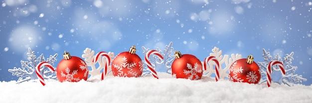Kartka świąteczna Z Ozdobnymi Bombkami, Cukierkami I Płatkami śniegu Na śniegu Premium Zdjęcia