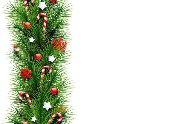 Kartka świąteczna, zielone gałęzie choinki, ozdobione kulkami, gwiazdkami, cukierkami i płatkami śniegu Premium Zdjęcia