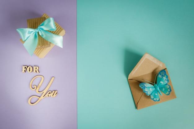 Kartkę z życzeniami dla ciebie na fioletowo - miętowym tle z pudełka, koperty i motyla Premium Zdjęcia