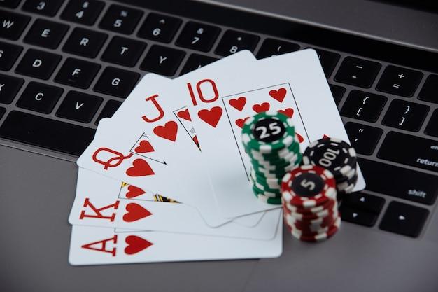 Karty Do Pokera I Stosy żetonów Pokerowych Na Komputerze Przenośnym. Koncepcja Kasyna I Pokera Online. Premium Zdjęcia
