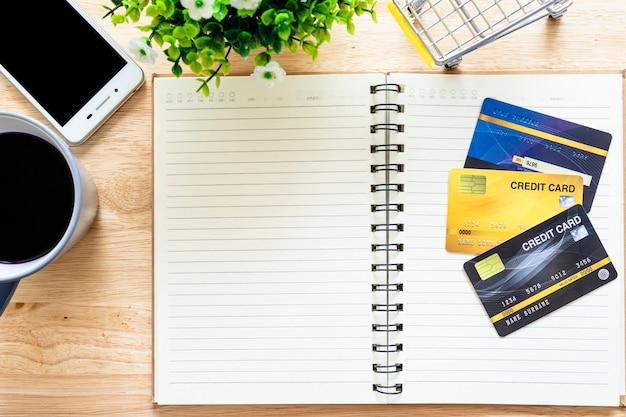 Karty Kredytowe, Notatnik, Doniczka, Smartfon, Wózek Na Zakupy I Filiżanka Kawy Na Drewnianym Tle, Bankowość Internetowa Widok Z Góry Stół Biurowy. Premium Zdjęcia