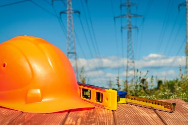 Kask Ochronny, Słuchawki, Rękawiczki Na Drewnianym Stole, Przed Słupkami Wysokiego Napięcia Premium Zdjęcia