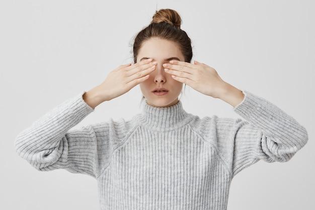 Kaukaska Dorosła Kobieta W Wieku 30 Lat Z Włosami W Bułce Zakrywająca Oczy Obiema Rękami. Skoncentrowana Dziewczyna Czeka Na Niespodziankę Z Zamkniętymi Oczami, Nie Wie, Czego Się Spodziewać. Język Ciała Darmowe Zdjęcia