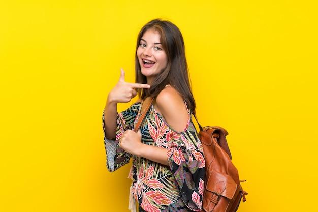 Kaukaska dziewczyna w kolorowej sukni nad odosobnioną kolor żółty ścianą z plecakiem Premium Zdjęcia