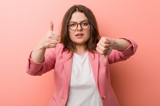Kaukaska kobieta biznesu plus size pokazuje kciuk w górę i kciuk w dół, trudny wybór Premium Zdjęcia