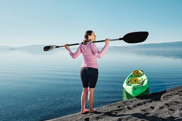 Kaukaska Kobieta Stojąca W Pobliżu Kajaka I Wody Jeziora Z Wiosłem Na Ramionach I Patrząca W Horyzont Premium Zdjęcia