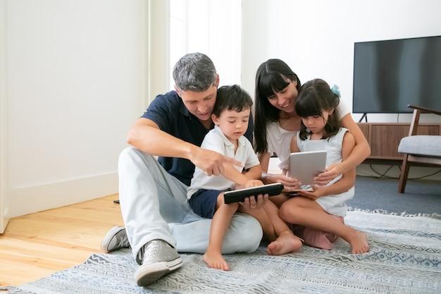 Kaukaska Mama I Tata Przytulanie Dzieci, Używanie Tabletów I Telefonu I Uśmiechanie Się. Darmowe Zdjęcia