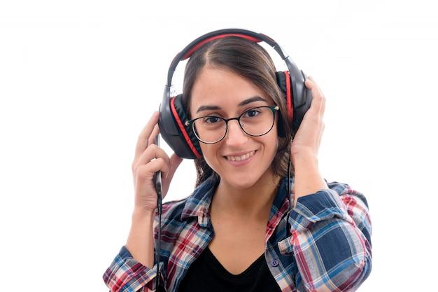Kaukaska młoda dziewczyna słucha muzyka z dużymi hełmofonami odizolowywającymi na białym tle Premium Zdjęcia