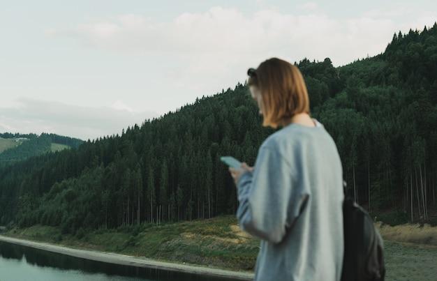Kaukaska Turystka Korzystająca Z Aplikacji Na Smartfona Z Mapami, Aby Znaleźć Drogę Do Lasów Iglastych Premium Zdjęcia