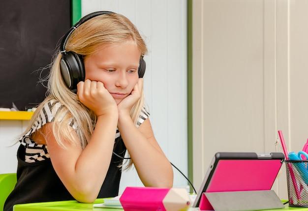 Kaukaska Urocza Uczennica Ze Słuchawkami Jest Na Nudnej Edukacji Domowej Online. Koncepcja Kształcenia Na Odległość. Skopiuj Miejsce Premium Zdjęcia