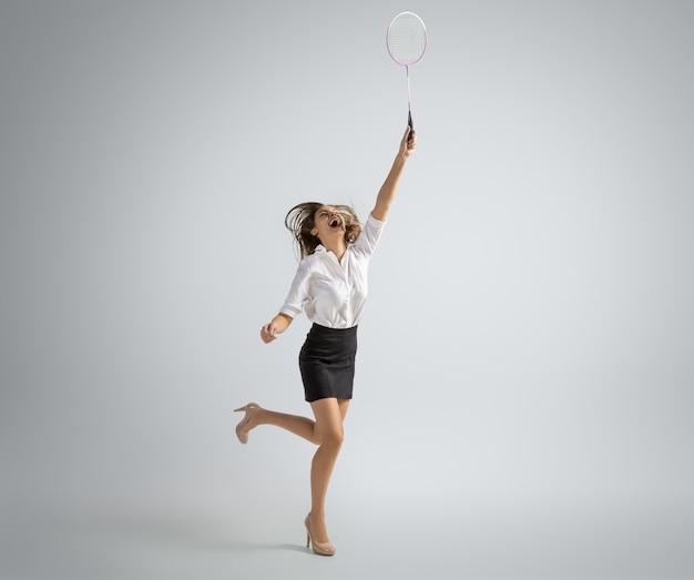 Kaukaski Kobieta W Biurze Ubrania Gra W Badmintona Na Białym Tle Na Szarej ścianie Darmowe Zdjęcia