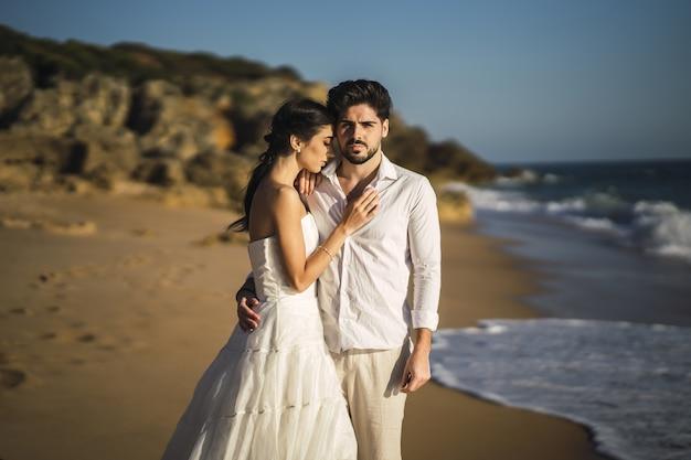 Kaukaski Kochająca Para Ubrana W Białe Ubrania I Przytulanie Na Plaży Podczas Sesji ślubnej Darmowe Zdjęcia
