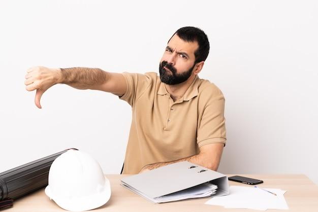 Kaukaski Mężczyzna Architekt Z Brodą W Tabeli Przedstawiający Kciuk W Dół Z Negatywnym Wyrazem Twarzy. Premium Zdjęcia