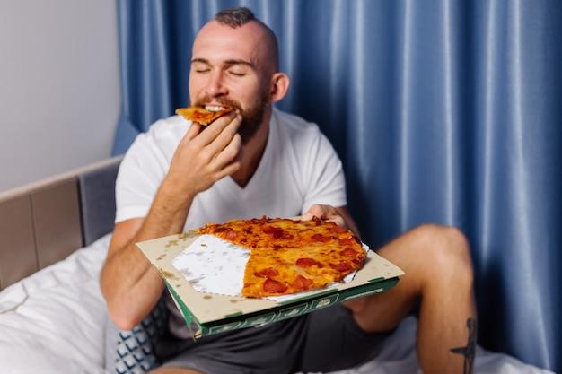 Kaukaski Mężczyzna O Fast Food W Domu W Sypialni Na łóżku Darmowe Zdjęcia