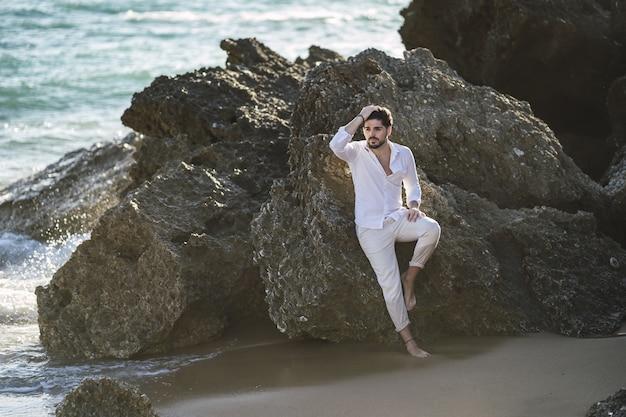 Kaukaski Mężczyzna Ubrany W Białe Szaty, Siedząc Na Kamieniu Na Plaży Darmowe Zdjęcia