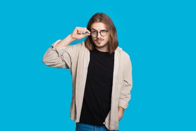 Kaukaski Mężczyzna Z Długimi Włosami, Dotykając Jego Okularów I Patrząc Na Kamery Na Niebieskiej ścianie Premium Zdjęcia