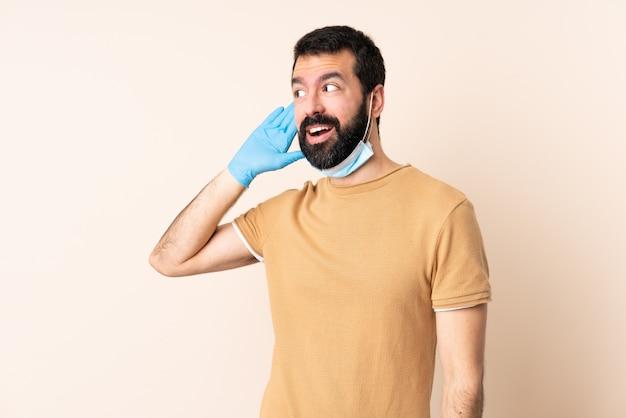 Kaukaski Mężczyzna Z Ochroną Brody Z Maską I Rękawiczkami Na ścianie Słucha Czegoś, Kładąc Rękę Na Uchu Premium Zdjęcia