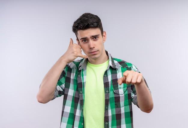 Kaukaski Młody Człowiek Ubrany W Zieloną Koszulę Pokazując Gest Połączenia I Gest Na Na Białym Tle Białej ścianie Darmowe Zdjęcia