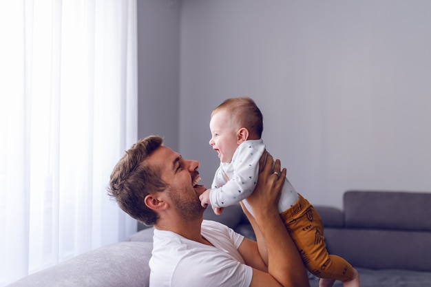 Kaukaski Młody Tata Podnoszenia Jego Kochającego Chłopca, Siedząc Na Kanapie W Salonie Premium Zdjęcia