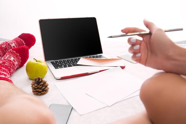 Kaukaski Para W Domu Przy Użyciu Technologii Internetowej. Laptop I Telefon Dla Osób Siedzących Na Podłodze Przy Kolorowych Skarpetkach. Darmowe Zdjęcia